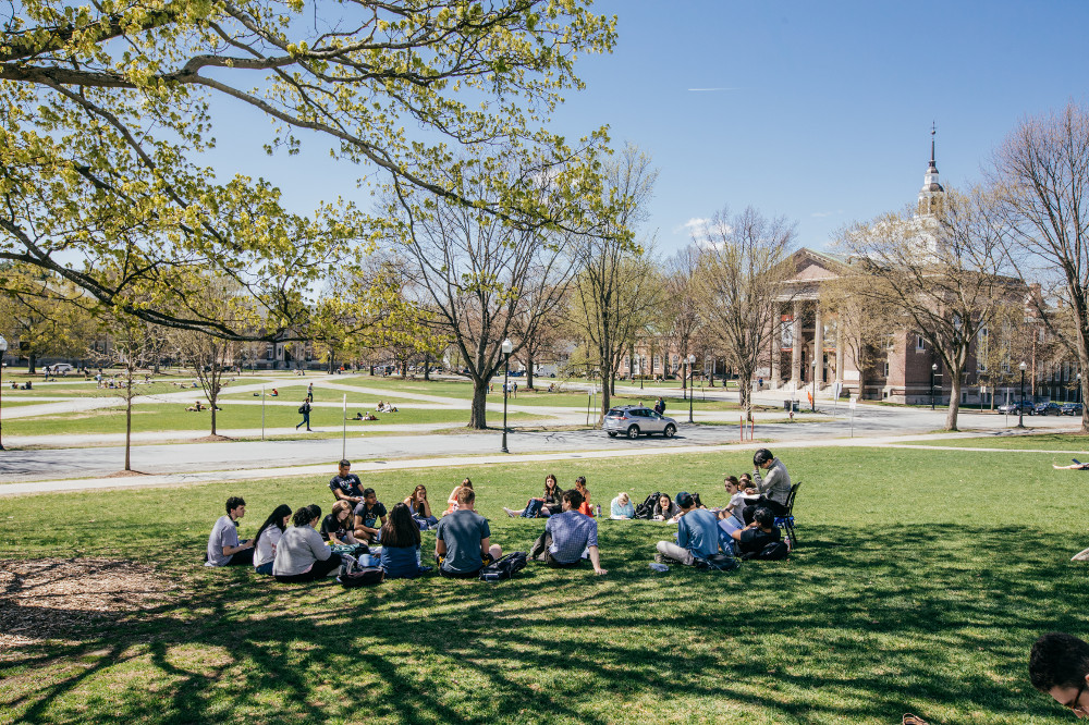 Students attend class outside Dartmouth Hall in the sunny spring weather.