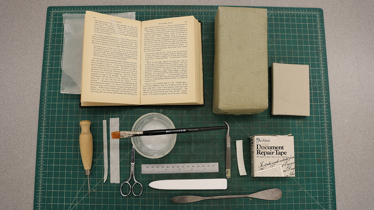 Book and repair supplies laid out on a mat