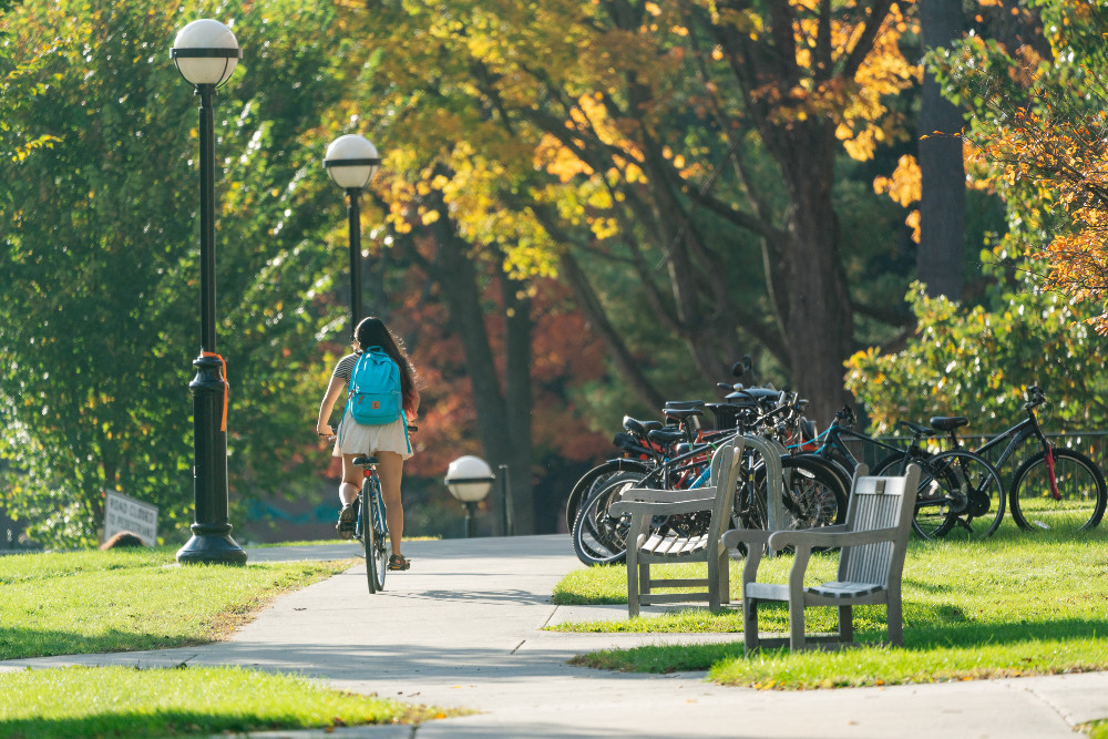A student rides a bike on campus during fall.