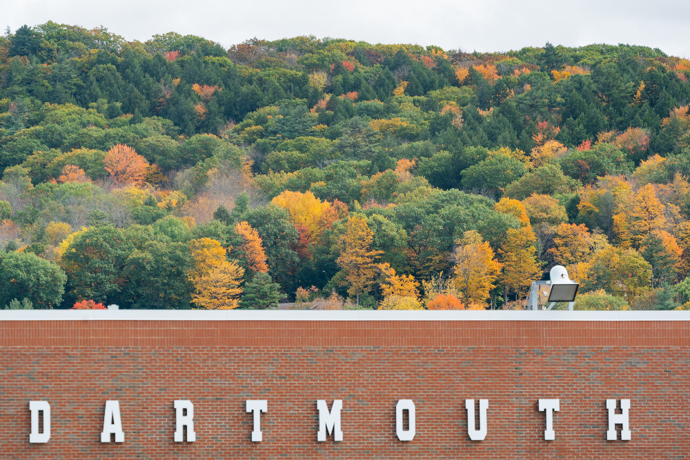 A Dartmouth sign on the stadium with fall foliage in the background.