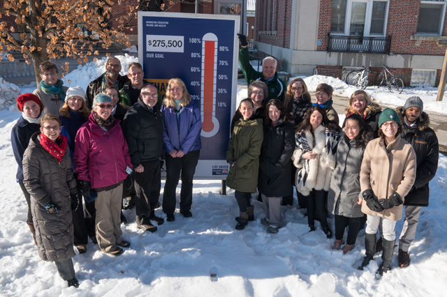 a group of people standing outside with the United Way donation thermometer