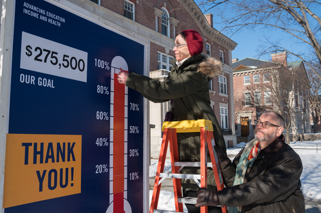 Gail Gentes and Rick Mills placing the final red stripe on the donation thermometer outside