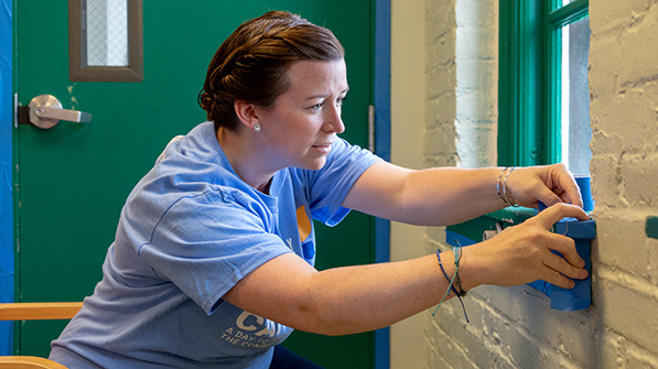 Brooke Sullivan laying blue painter's tape on a green windosill