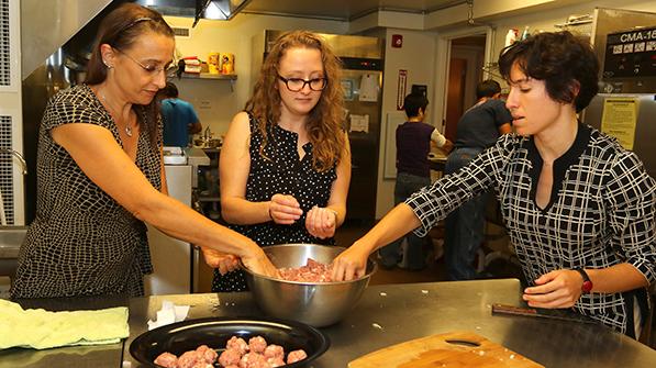 three women in a kitchen rolling meatballs