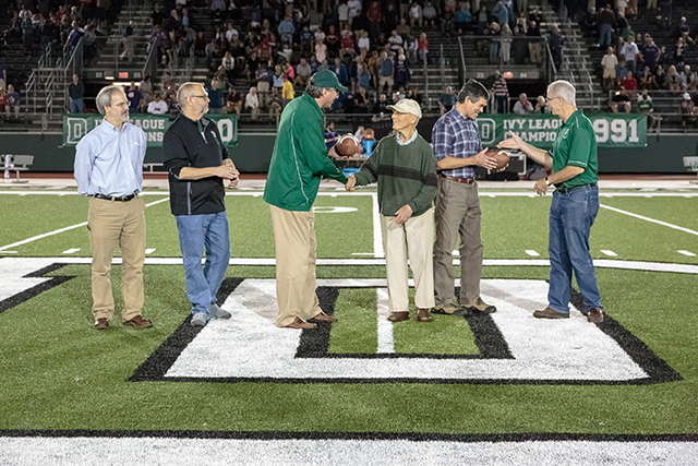 Rob Schultz, Rick Mills, Harry Sheehy, and President Phil Hanlon hand a football to Dr. Robert Norman and Win Piper