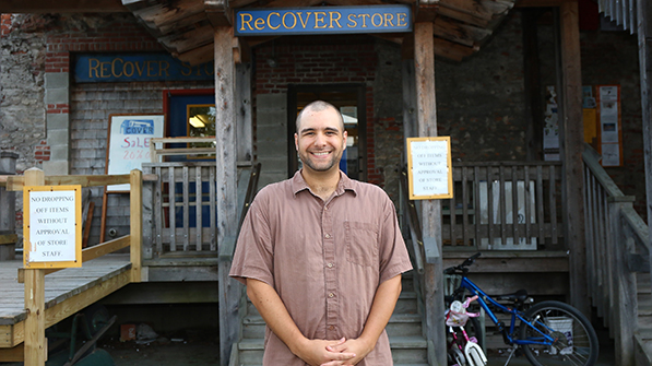 Josiah Proietti standing at the entrance to the Cover Home Repair ReCover store