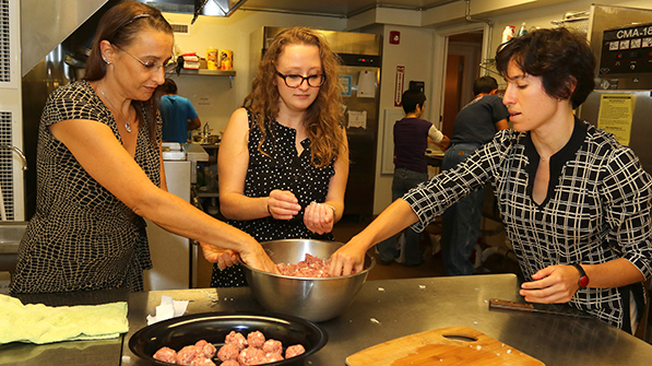 three women in a kitchen rolling meatballs